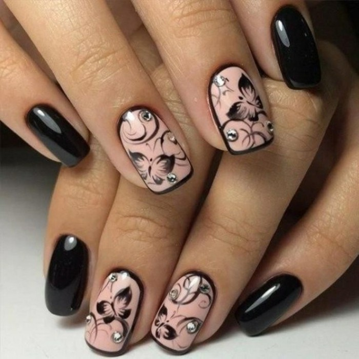 bling bling nails, eight fingers with nails painted in black and pink, pink nails have black butterfly decorations and rhinestones