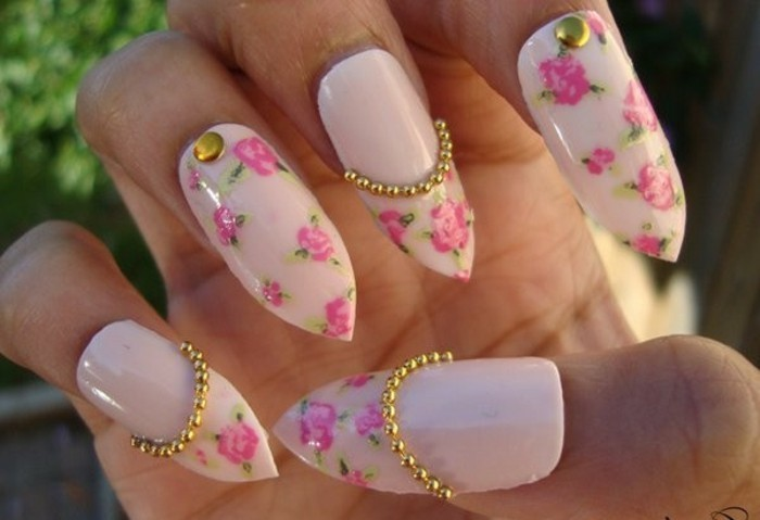 bling bling nails, close up of long, sharp fake nails, painted with pale pastel pink nail polish, and decorated with rose stickers and gold details