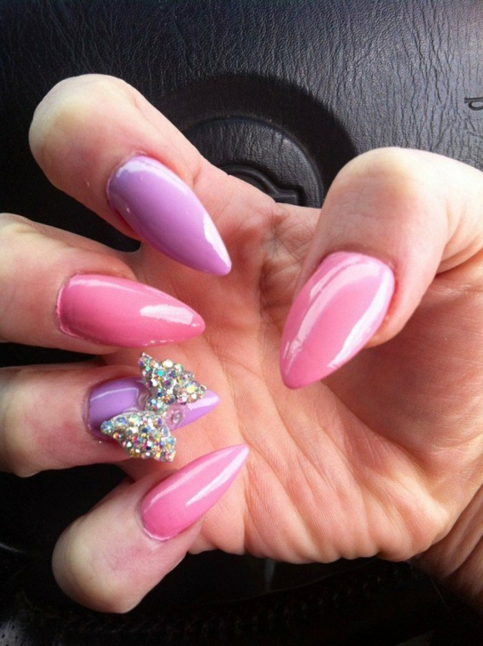 bling bling nails, close up of hand with sharp, pastel pink and pale lilac nails, one of which has a rhinestone bow decoration