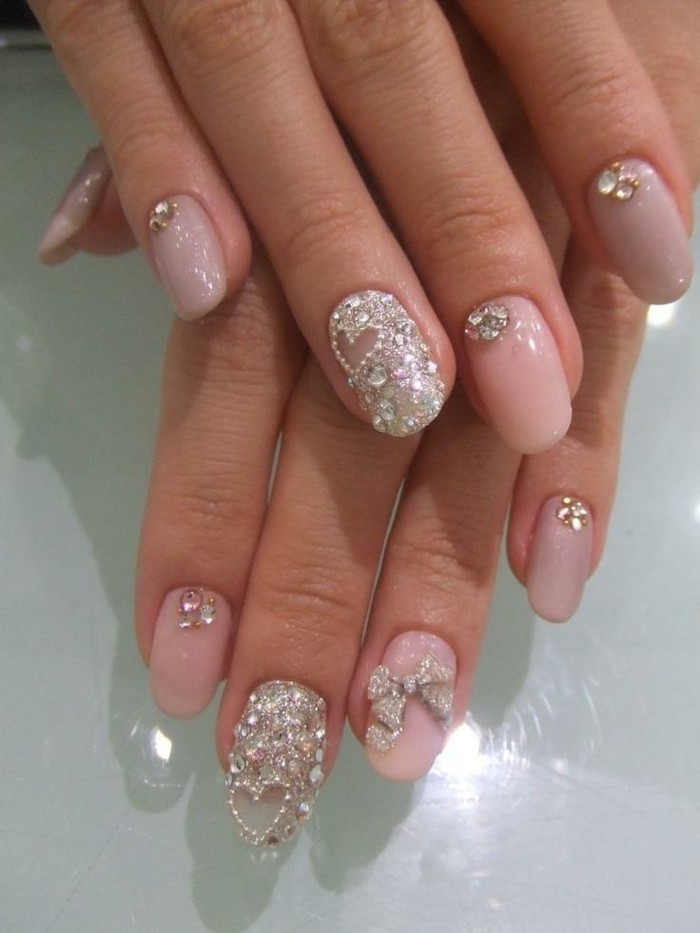 nail designs with rhinestones, round nails painted with pale pink polish, decorated with rhinestones on every finger, ring fingers' nails are entirely covered with rhinestones, and have a heart detail