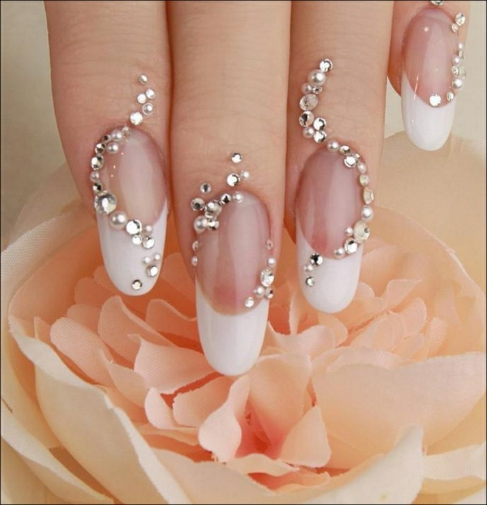 french manicure with long white tips, both nails and finger tips decorated with rhinestones
