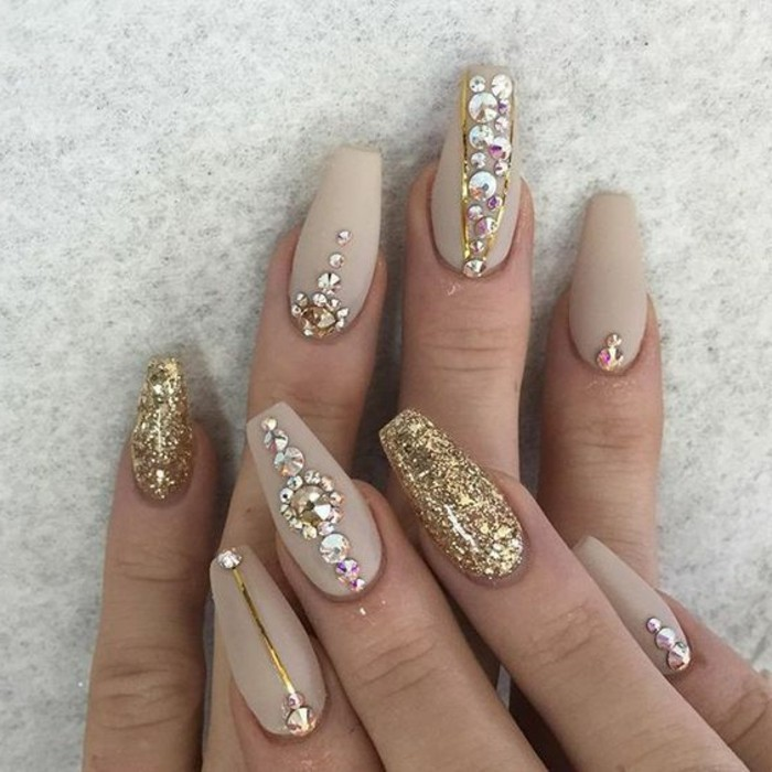nude nails with rhinestones, close up of two hands with pale nude matte nail polish, two nails covered in gold glitter, the rest have rhinestones