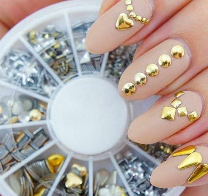 bling bling nails, four long round nails with nude nail polish, decorated with golden 3D stickers, box with more stickers in the background