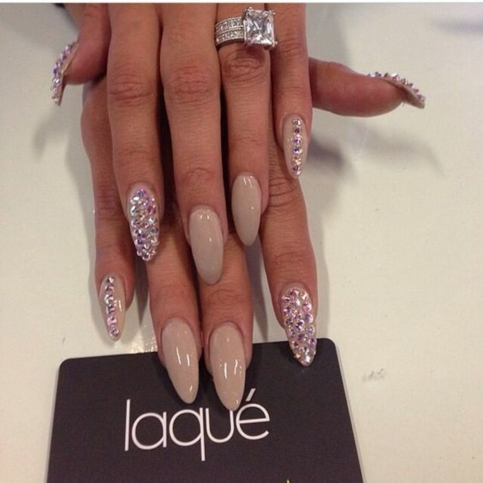 nude nails with rhinestones, long round nails with nude polish, index pinkie and thumb nails decorated with rhinestones