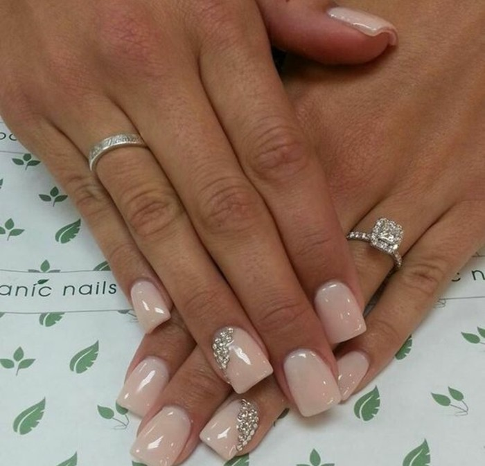 nude nails with rhinestones, square nails painted in nude polish, two decorated with rhinestones