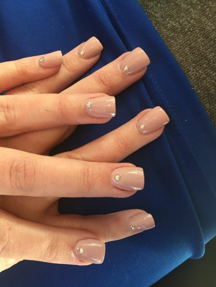 nude nails with rhinestones, close up of two hands with nude nail polish, one rhinestone on each nail