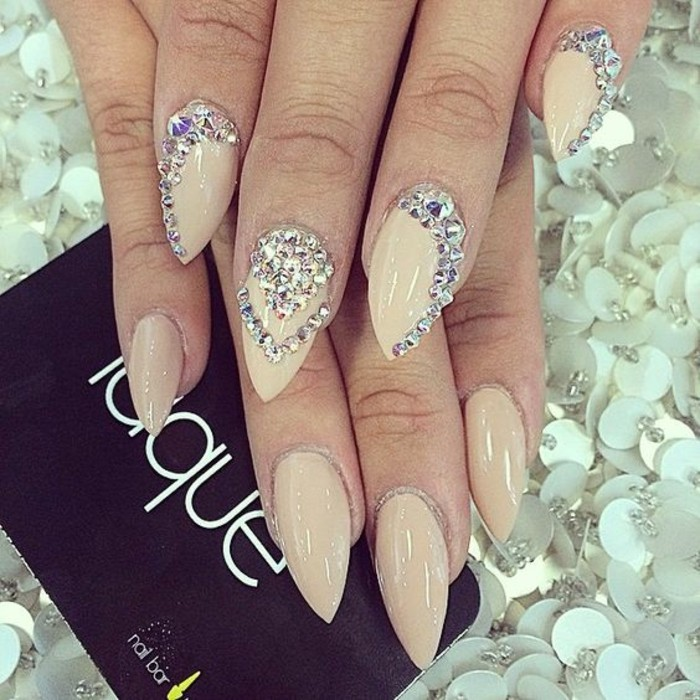 nude nails with rhinestones, sharp manicure in nude tones, decorated with many rhinestones on one hand and plain on the other
