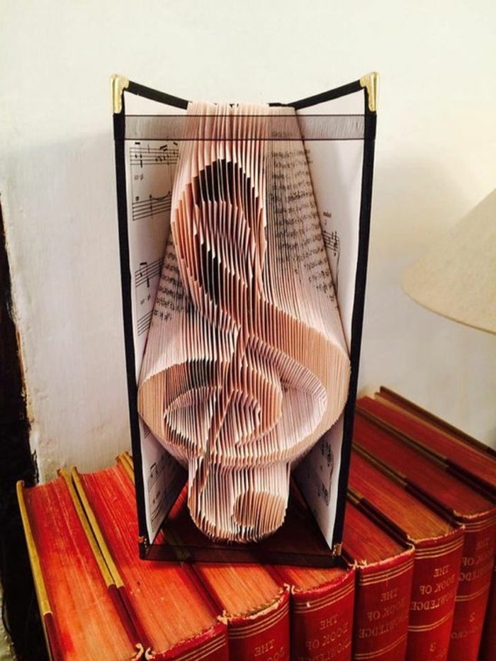 treble clef shape, made from folded pages, inside a book with hard black covers and golden edges, containing musical notes, and decorated with sheer black ribbon