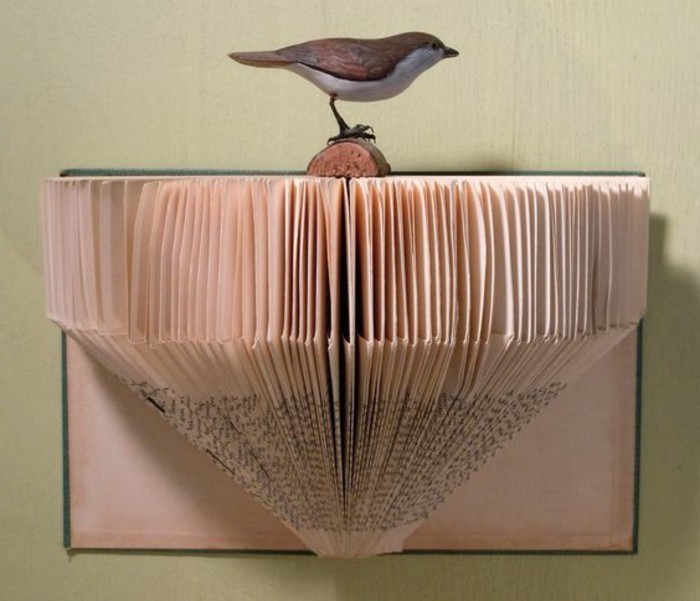 paper art, created from cut and folded vintage book pages, stuck to one of the book's covers, decorated with realistic bird ornament