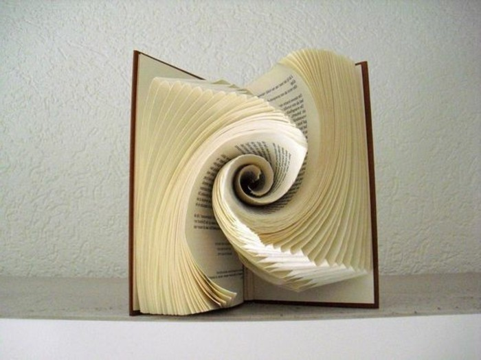 opened book with brown hard covers, containing paper art, made from folded pages, shaped into a swirling round pattern