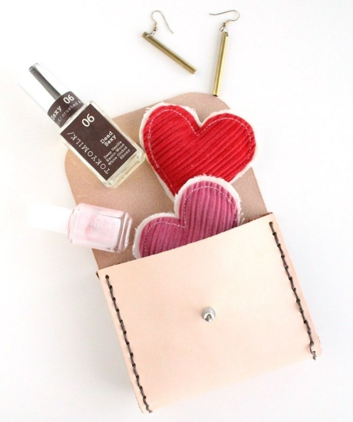 what to get your best friend for her birthday, small open hand-stitched cream leather purse, heart ornaments, nail polish bottles and earrings pouring out