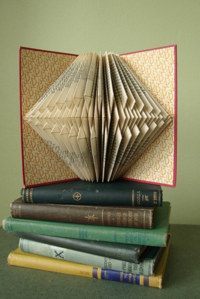 vintage book with red hard covers, placed on a pile of vintage books, and opened to reveal geometrical pattern, created from many folded pages