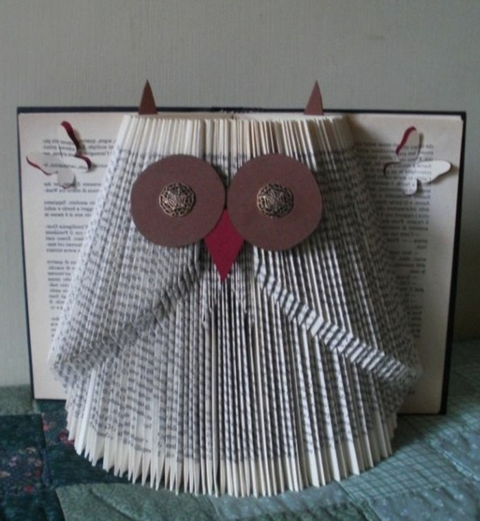 owl ornament decorated with felt cutouts and metal buttons, made from folded pages, inside an open book with dark hard covers, and butterfly-shaped cutouts