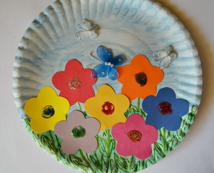 diy art projects, white paper plate, decorated with blue and green crayon, colorful flower-shaped cutouts, and small butterfly ornaments