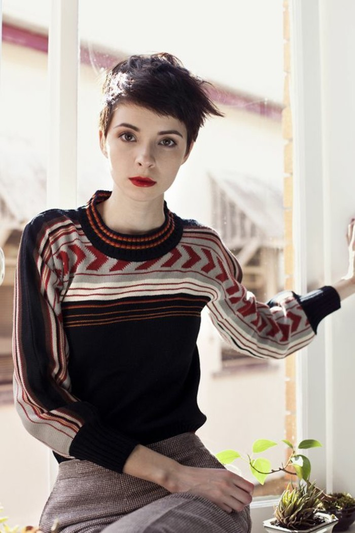 hairstyles for short hair, slim young woman with dark short hair, bangs brushed to one side, bright red lipstick and navy, white red and grey sweater