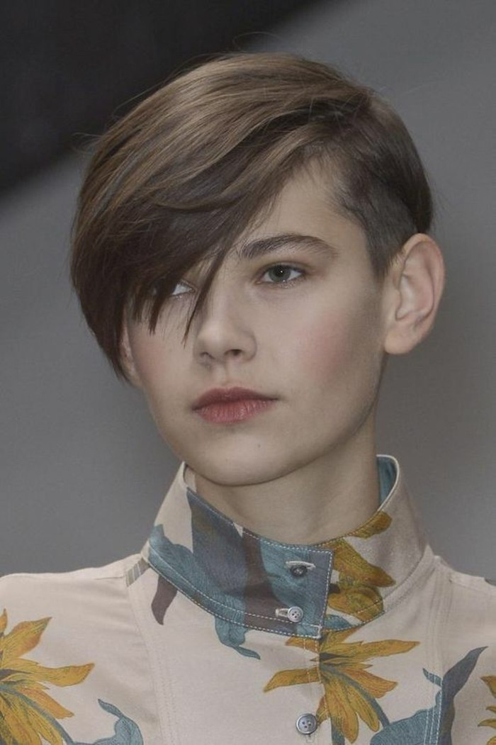 pixie cut, young woman with brown hair and masculine haircut, side bangs falling over one eye, wearing floral top