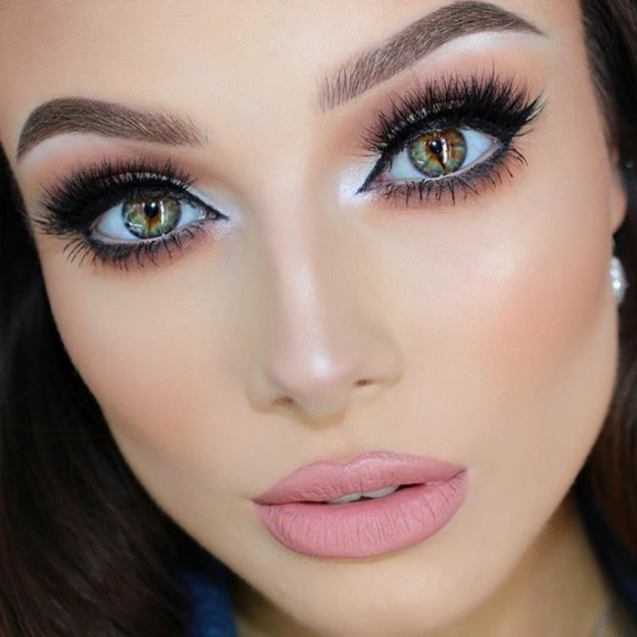 different colored eyes, woman with heavy make up, fake lashes and black eyeliner, silver eye shadow and pink matte lipstick