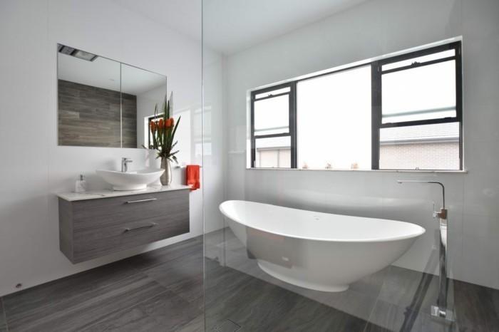 bathroom ideas photo gallery, grayish-brown wooden floor, white tub behind glass wall