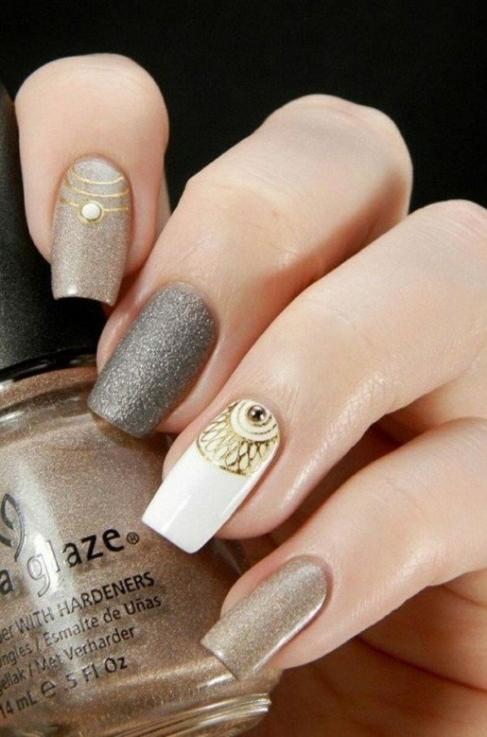 rhinestone nail art, hand holding bottle of pale brown shimmering nail polish, hand's nails painted in similar colors, with gold details, one rhinestone and a white accent