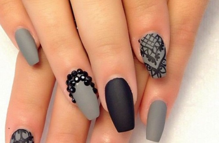 rhinestone nail designs, close up on fingers with grey and black matte nails, decorated with black drawings and stones