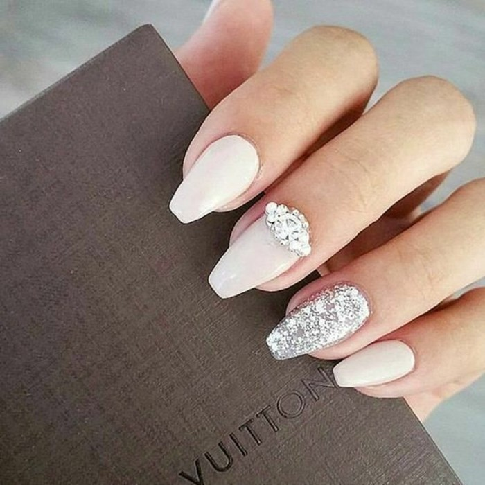 rhinestone nail designs, hand with pale pink and silver glitter nail polish, decorated with rhinestones, holding brown object