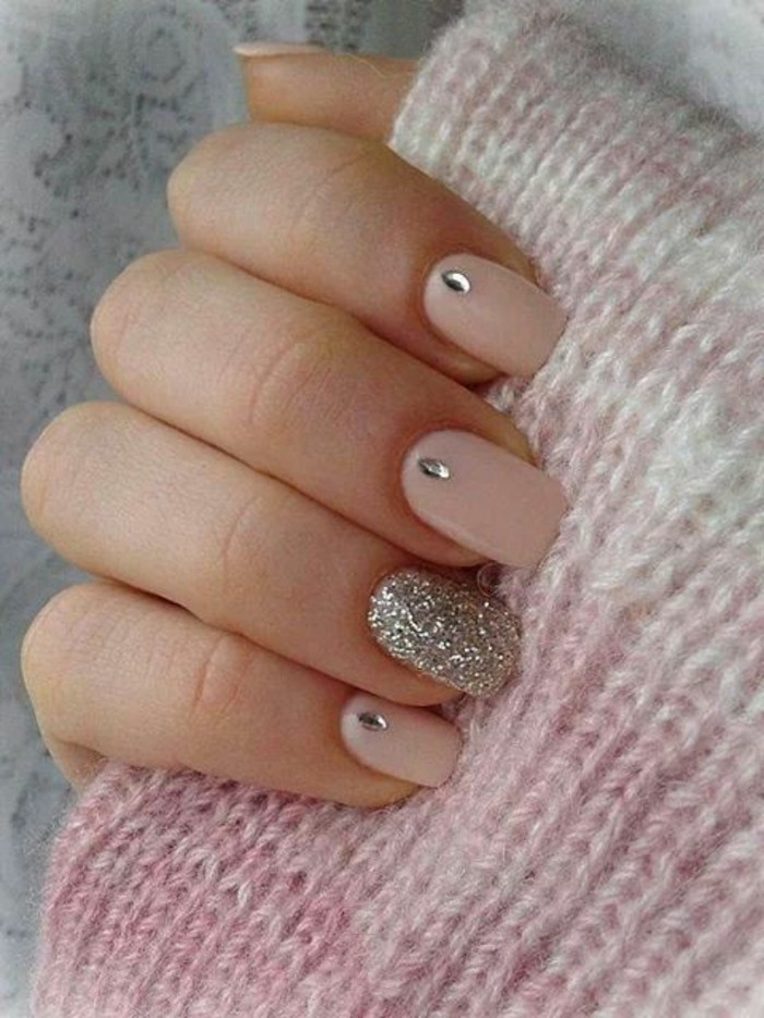 rhinestone nail designs, close up of hand holding pink woolen fabric, four nails painted in pale pink with rhinestone details, one decorated with silver glitter
