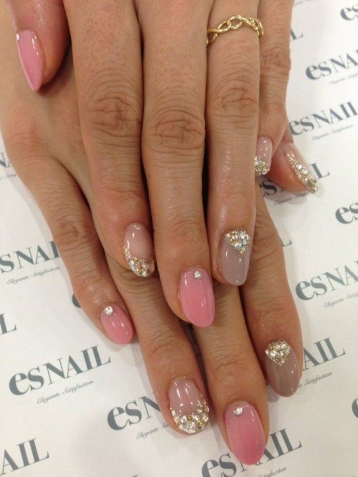 rhinestone nail art, two hands with fingernails painted in different shades of pastel pink, decorated with glitter and rhinestones