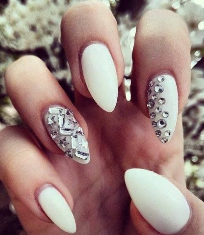 nail designs with rhinestones and glitter, close up of hands with sharp nails painted in milky white polish, two fingers decorated with round, star-shaped and rectangular rhinestones