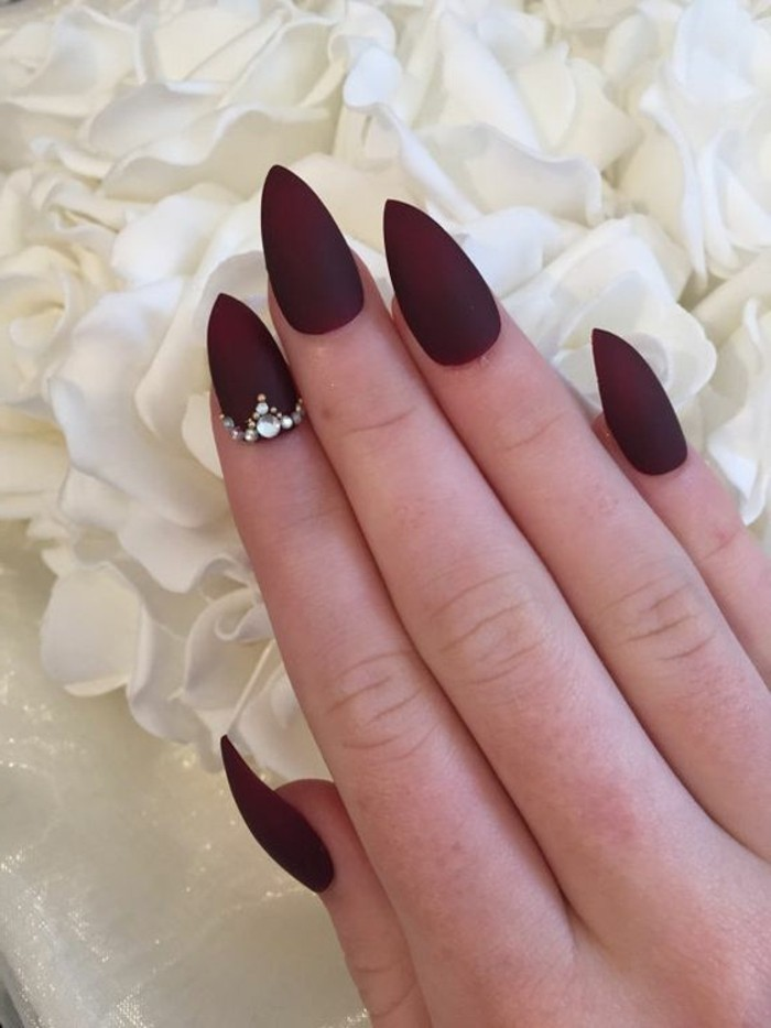 nail designs with rhinestones and glitter, hand with sharp nails painted with deep red matte polish, one nail decorated with several rhinestones