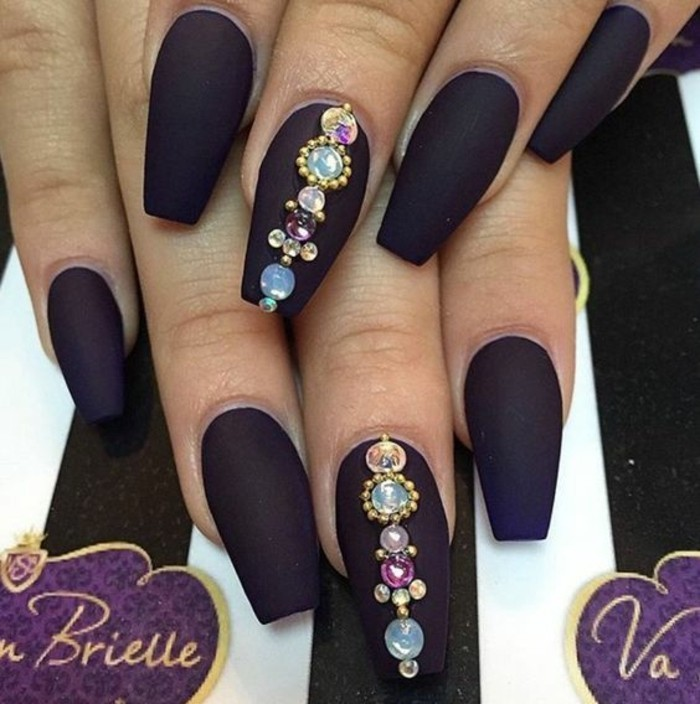 nail designs with rhinestones and glitter, two hands with dark purple square nails, two decorated with multicolored rhinestones