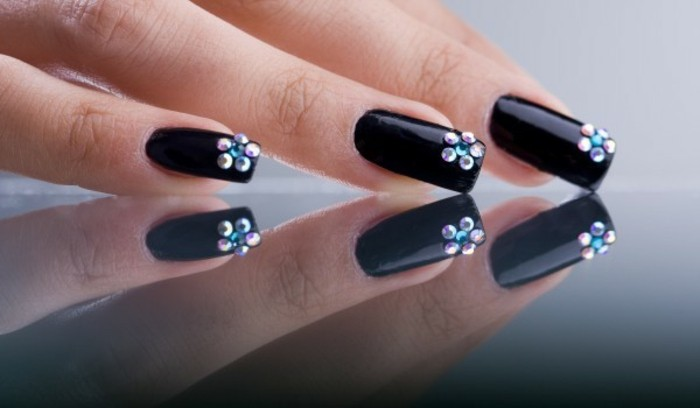 rhinestone nail designs, three fingers resting on a reflective surface, with black nails decorated with rhinestone flowers