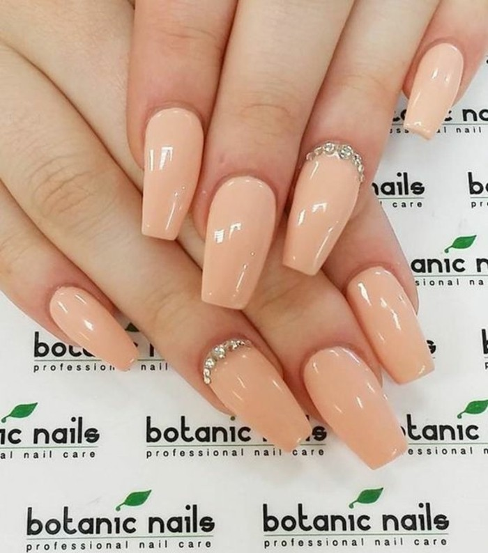 nude nails with rhinestones, two hands with nails painted in pale nude polish, two decorated with several rhinestones