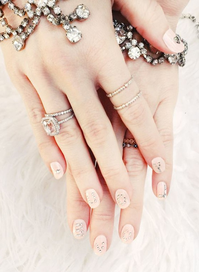 nail designs with rhinestones and glitter, two hands with rings and bracelets, with round nails painted in pale pink polish, each decorated with several rhinestones