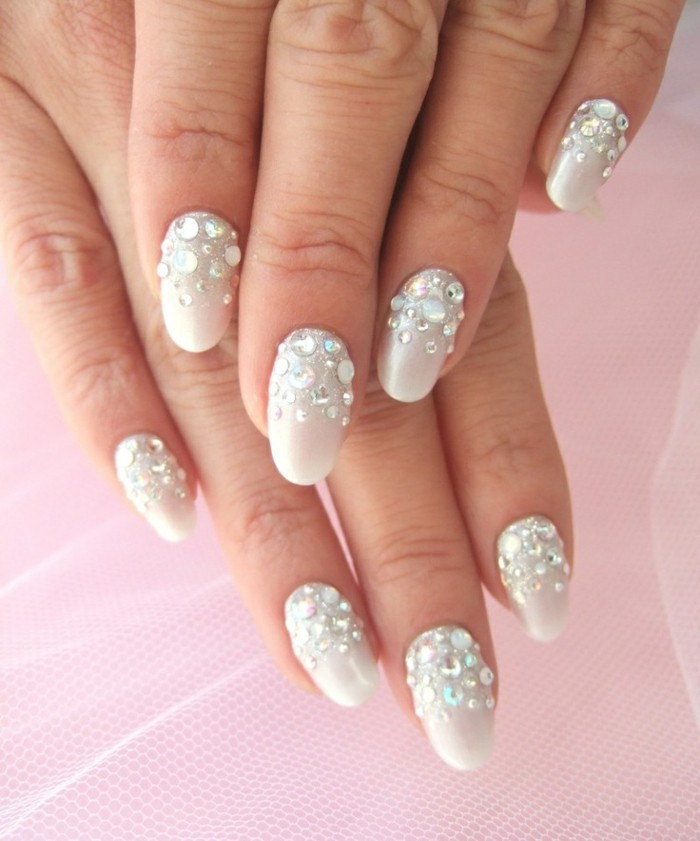 hands with round nails, painted in creamy white nail polish, decorated with round, silvery white rhinestones