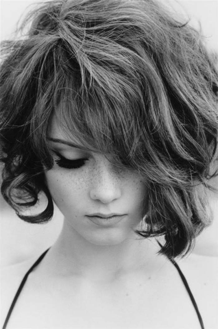 haircuts for women, black and white image of young woman, with 1960s style short hair, looking down, side bangs and fake eyelashes