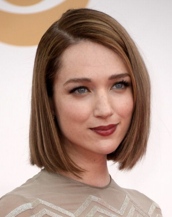 haircuts for women, smiling woman with straight, side-parted dark blonde bob, with red lipstick and a nude-colored top