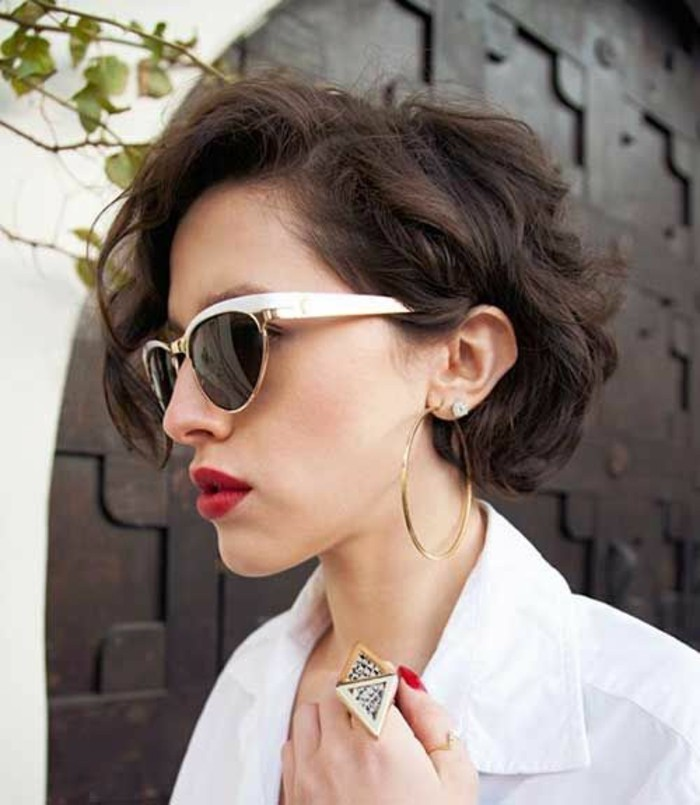 haircuts for women, woman with dark brown, side-parted curly hair, wearing sunglasses with white frames and bright red lipstick