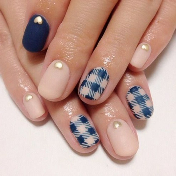 two hands with short nails, painted in pale pink and dark blue matte polish, with tiny gold hearts and chequered detail