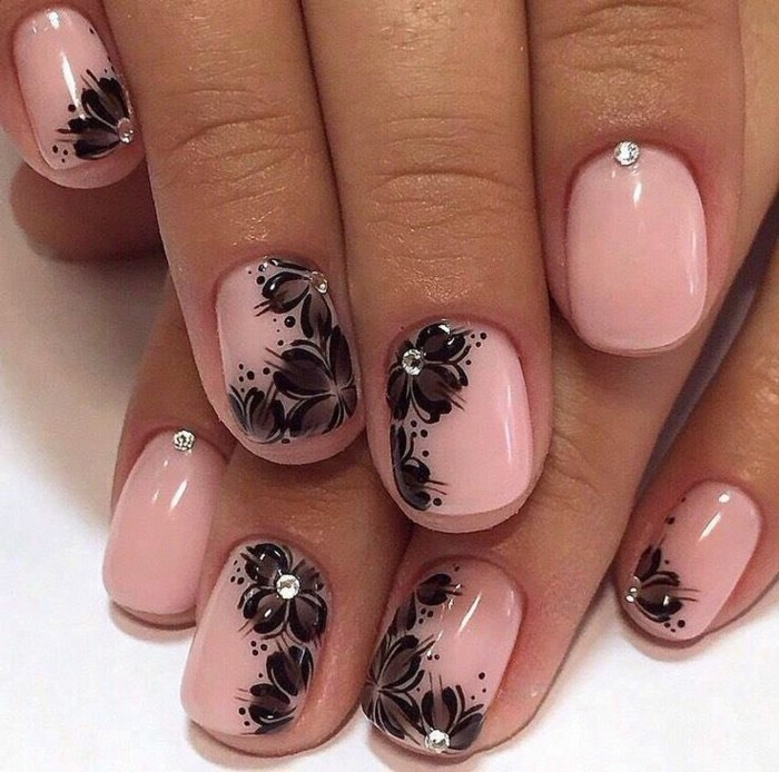 close up of pale pink nails, decorated with black painted flowers, and tiny rhinestones