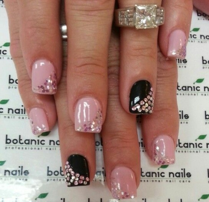 bling nail designs, two hands with short square nails, painted in pink and black, each decorated with rhinestones