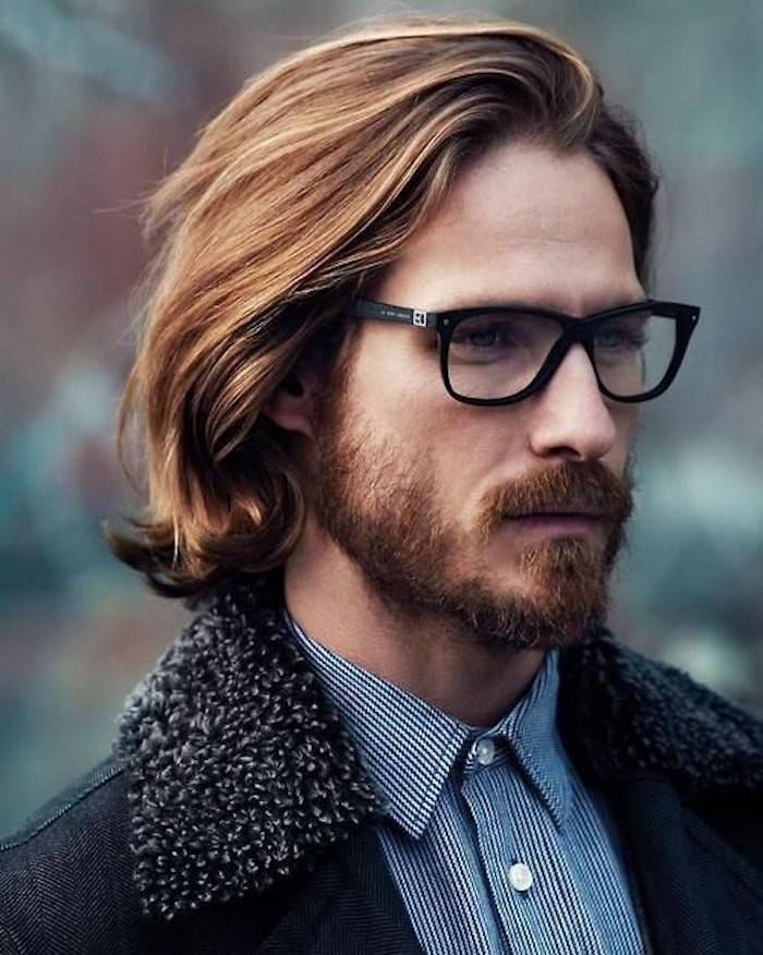 shoulder length hair, auburn haired man with glasses, mustache and beard, blue pinstriped shirt and coat