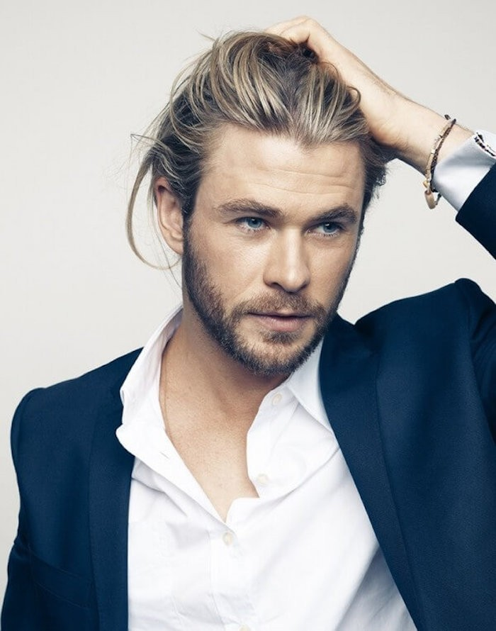 medium length hairstyles, Chris Hemsworth holding his hair with one hand, wearing dark blue blazer and white shirt