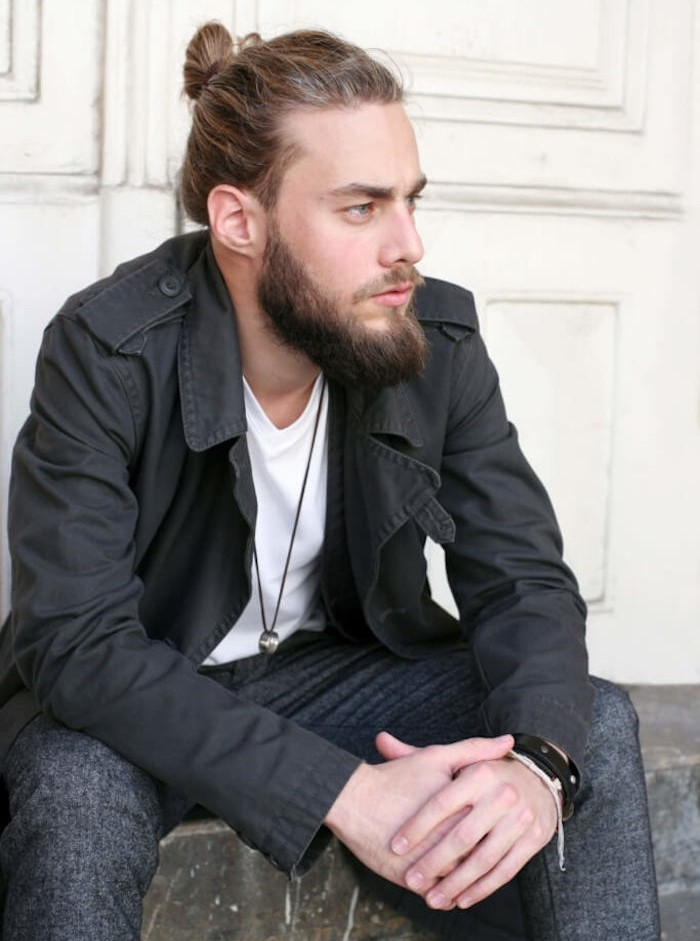 medium length hair, sitting dark blond man, hair tied in a man bun, mid-length beard and mustache
