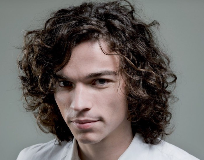 shoulder length haircuts, smiling curly man in white shirt, messy brown hair