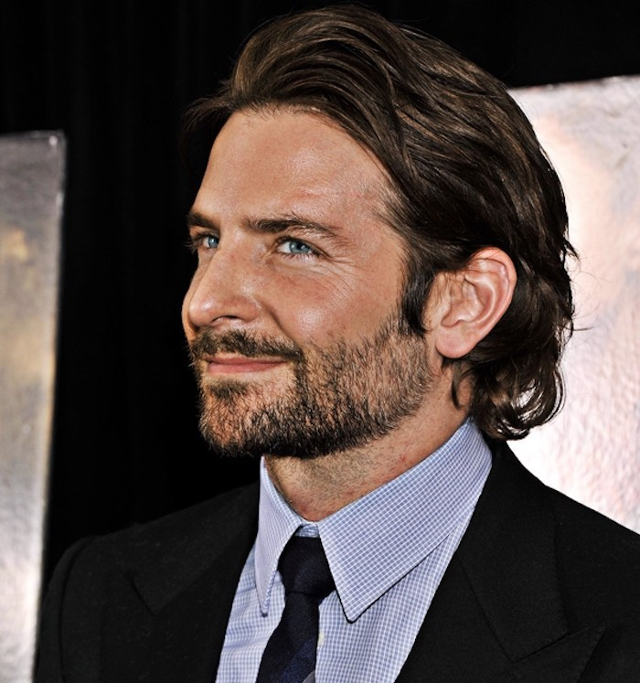 medium length hair, smiling man with stubble beard, dressed in suit and tie, wavy hair slicked back and tucked behind ear
