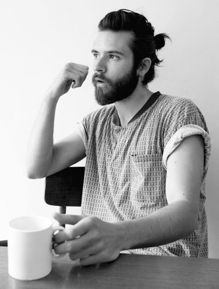 shoulder length hairstyles, bearded man sitting at a table, holding white mug, hair tied in man bun