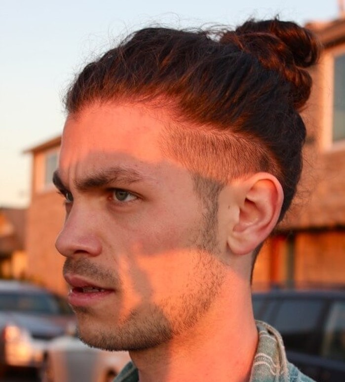 hairstyles for shoulder length hair, serious looking man, with stubble beard and mustache, short undercut and man bun