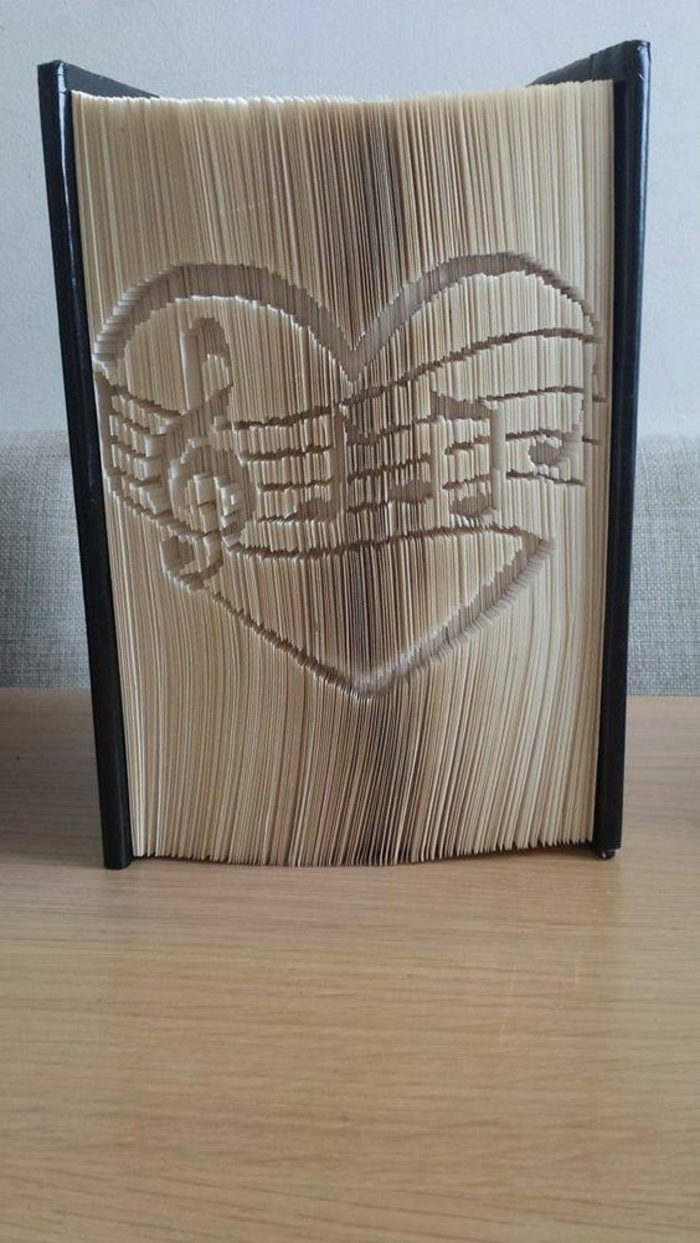 a heart shape with several musical notes, carved into the pages of a thick closed book, with shiny black hard covers