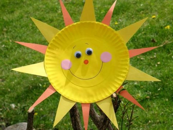 yellow paper plate, decorated like a smiling sun, with rays made from yellow and orange felt, pink cheeks and stick-on eyes