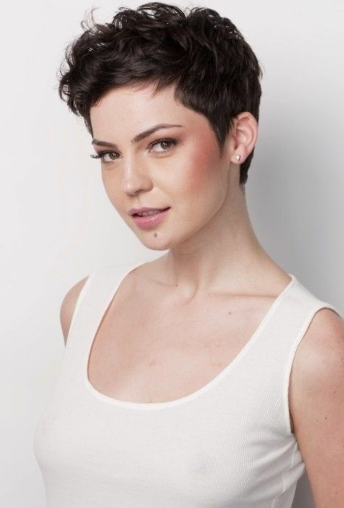woman with very short and curly, dark brown masculine haircut, wearing white tanktop